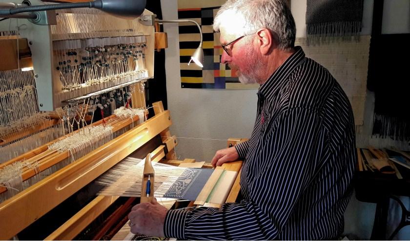 Teun Hoogeveen achter zijn weefgetouw, dat hij geschikt gemaakt heeft voor damastweven, zodat hij figuren kan weven in zijn doeken.