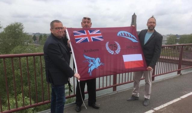 Karl van den Top en Kevin van Guilik overhandigen het eerste exemplaar van de Herdenkingsvlag aan Marcel Legerstee. (Foto: Ome Joop's Tour)