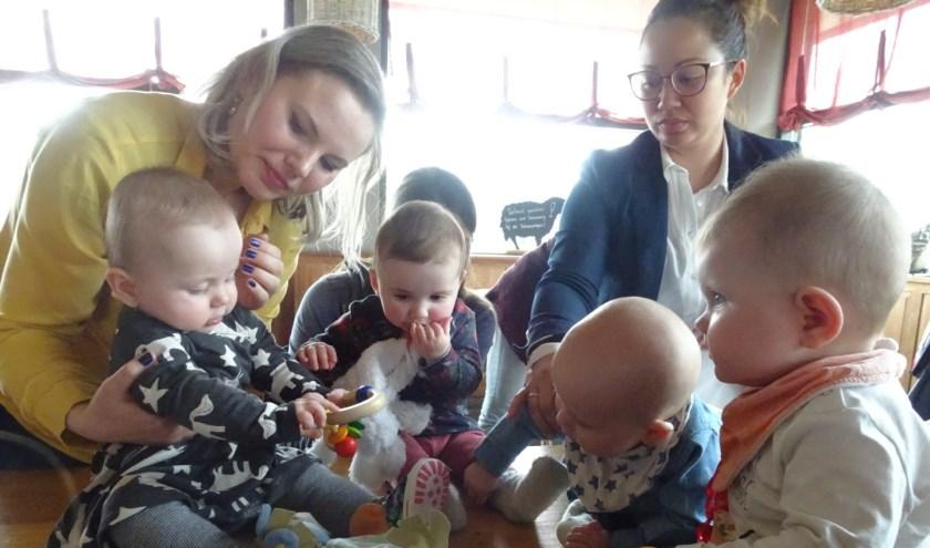Met hun baby's op schoot wisselen de moeders ervaringen uit en drinken een kop koffie.