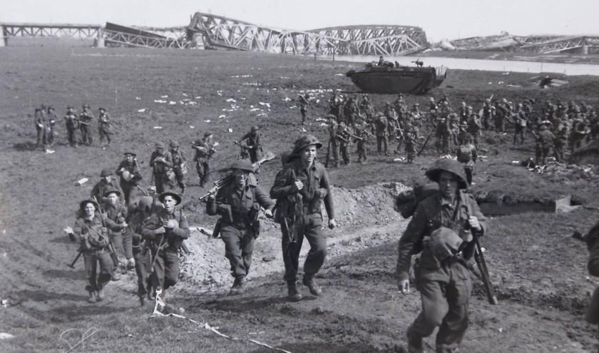 Bekend beeld van de overtocht van Britse en Canadese soldaten bij de Veerdam in Westervoort. Op de achtergrond de vernielde IJsselbrug.