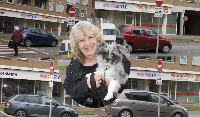 Annemieke Speek met hondje Toby. Op de achtergrond: de ene na de andere automobilist negeert het inrijverbod. (foto Gert Perdon)