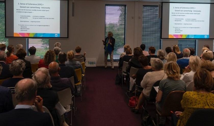 De aanwezigen luisteren naar de lezing van Machteld Huber over positieve gezondheid en veerkracht.