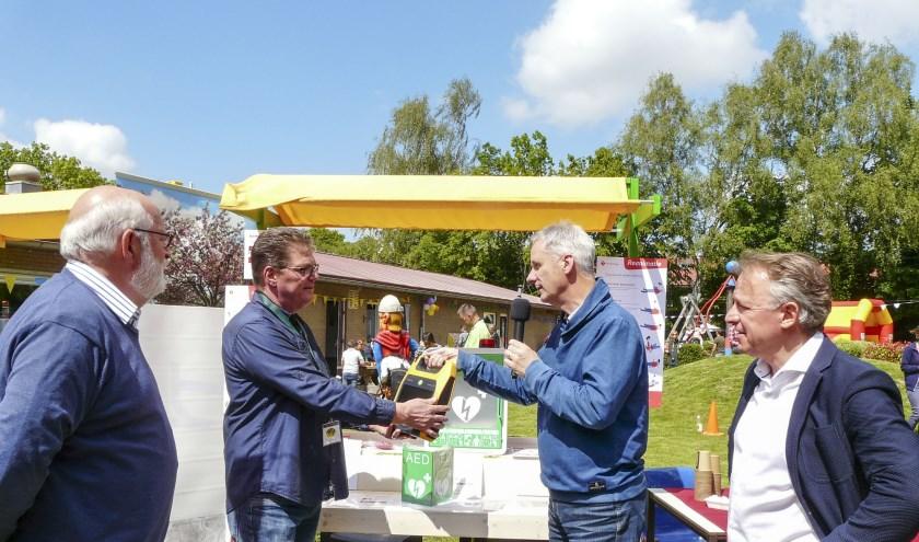 Peter Paul Tonen (Lionsclub), overhandigt de AED aan Geert Engelen (speeltuin Tuindorp). Naast hem staat Frans Seesing (Stichting Jan van Berkum) en  Bas Arents (Lionsclub). (Foto: Bob Nagel - PR-LCW)