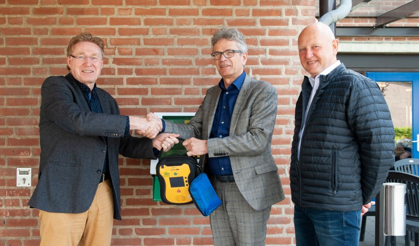 Johan Esendam, voorzitter van Hart4Winterswijk, Marcel Duvigneau, bestuurder van Marga Klompé en Wim Kos van Hart4Winterswijk staan. Zij staan voor de AED bij Pronsweide.
