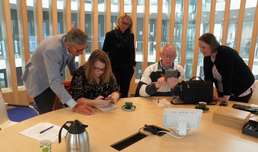 Fortuyn en de dames Van den Heuvel (achter) en Van den Nouland (r) laten journalisten zien hoe simpel de app werkt. Foto Kees van Rongen