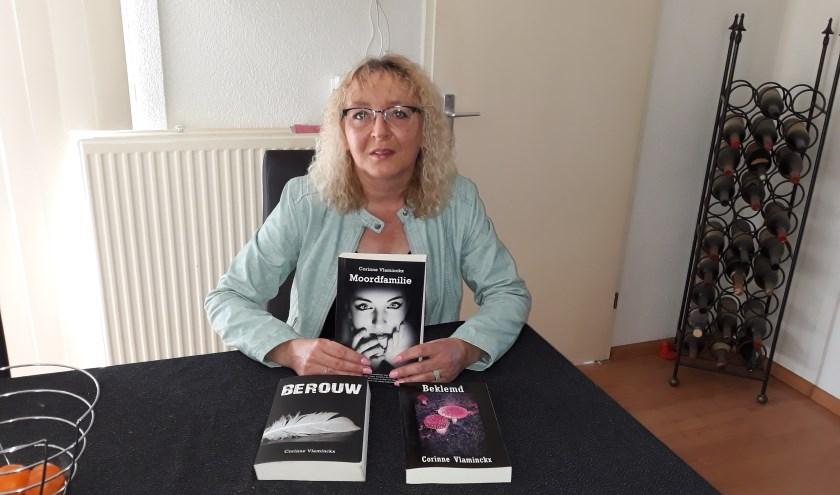 Corinne Vlaminckx toont trots haar verzameling uitgebrachte thrillers, met haar debuut 'Moordfamilie' in haar hand.
