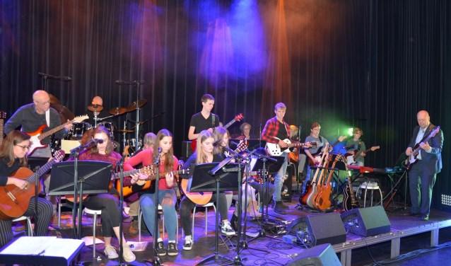 Optreden van Sjaak van de gitaar en ukelele school en de leerlingen tijdens zijn jubileumconcert: 40 jaar gitarist