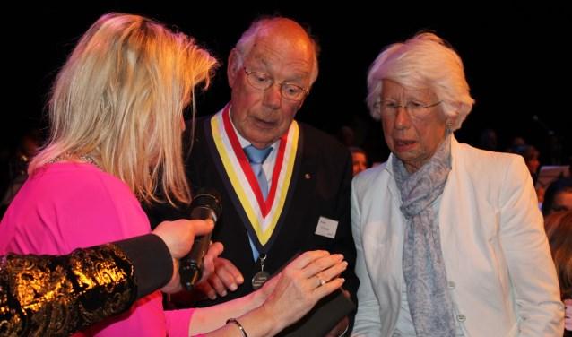 Burgemeester Koops geeft tekst en uitleg over de versierselen bij de zilveren erepenning aan het echtpaar Hogenbirk