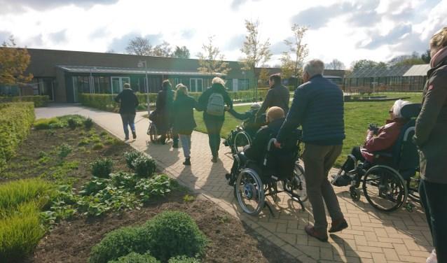De vrijwilligers wandelen met de bewoners van Pronsweide