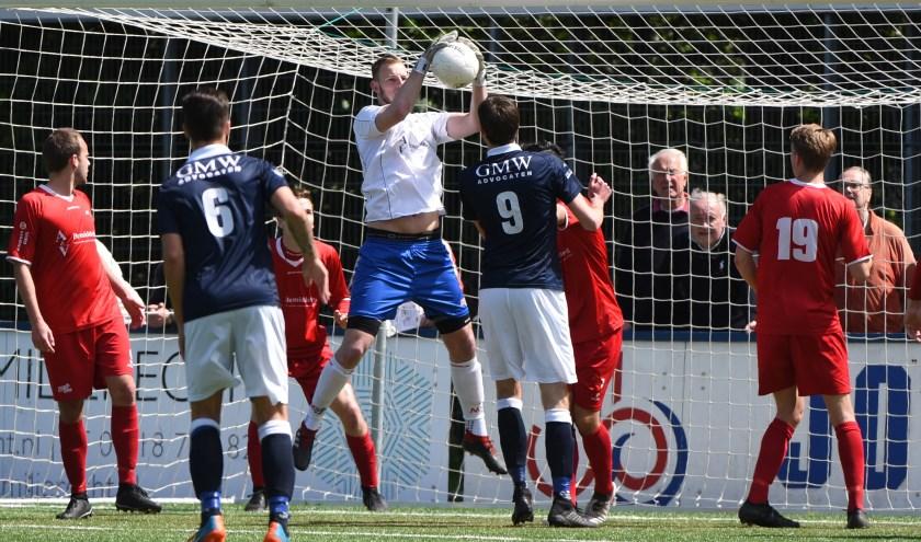 Keeper Dani Centen pakt de bal klemvast voor Frank van der Heiden (9) in een vol strafschopgebied. (Foto: Marcel de Kler)
