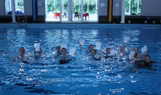 De negen jonge snorkelduikers (met hun snorkelbrevet) en hun trainers vieren feest in het water. (foto: PR)
