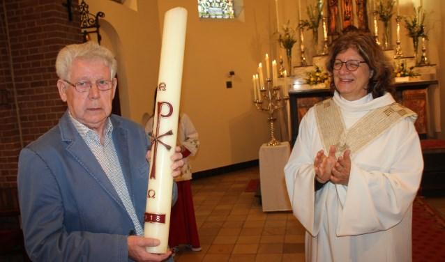 De paaskaars werd Herman Snoeijink overhandigd door pastor Ingrid Schraven na de hoogmis.