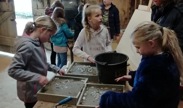 Kinderen leggen hun eigen keitjesvloer, waarvoor de vloer van museumboerderij de Vuurrever als voorbeeld dient.
