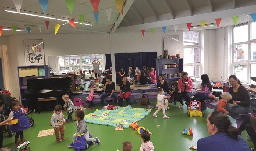 Een overzicht van het Baby Peuter Café Westervoort op een dinsdagochtend in IKC De Hoge Hoeve. Kinderen en ouders vermaken zich opperbest.