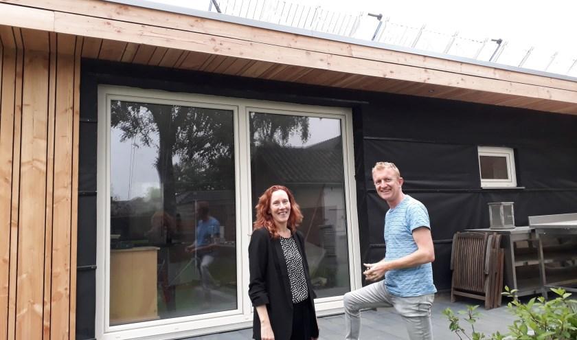 Maaike en Eric voor hun aanbouw van stro en leem. Links is de dampopenfolie al met hout afgewerkt, rechts moet dat nog. (foto: Ceciel Bremer)