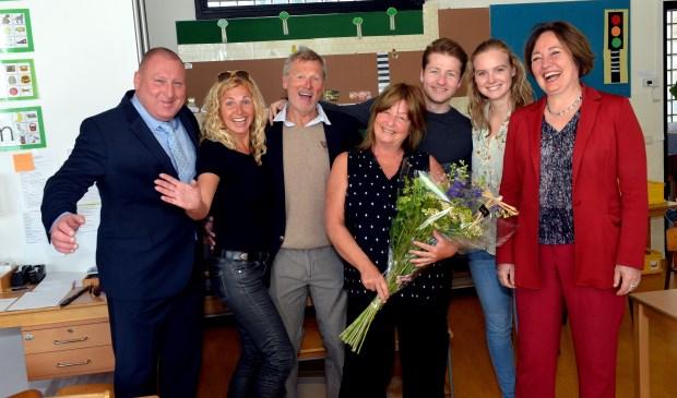 Kleuterjuf Iris Ewbank - De Ruyter (met bloemen) omringd door haar familieleden, directeur (links) en wethouders Saskia Bruines (rechts).
