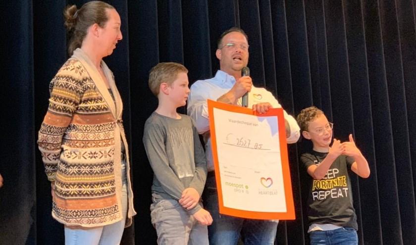 Directeur en leerling van De Moespot reiken cheque uit aan voorzitter en zoon van stichting Heartbeat