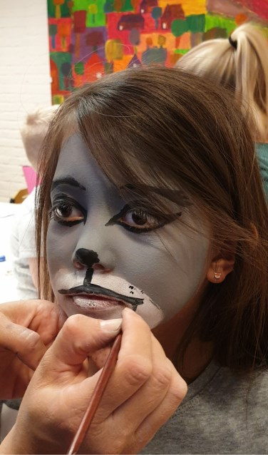 Een van de kinderen wordt als wolf geschminkt.
