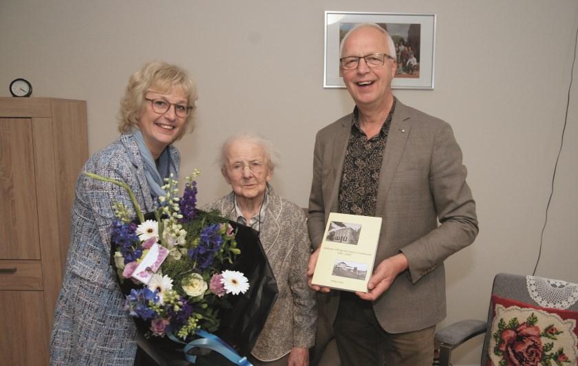 Diny en Martin Wieleman overhandigen het boek 'Wieleman, 100 jaar een begrip in Westervoort' aan de 100-jarige Riek Oversteeg.