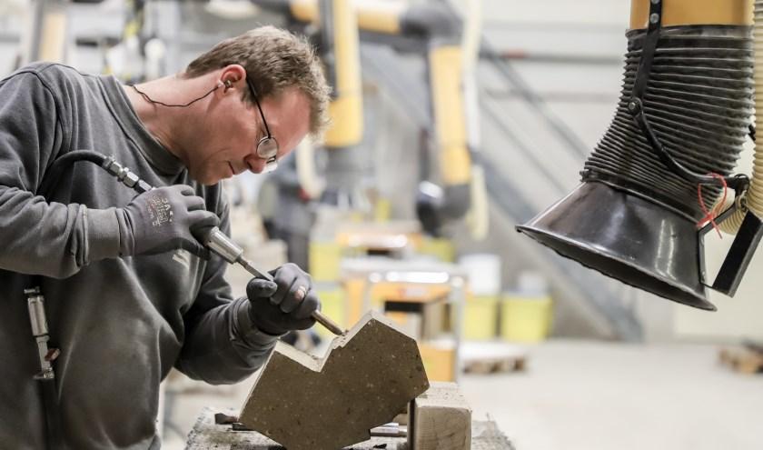 Een medewerker van Slotboom Steenhouwers aan het werk in de werkplaats.