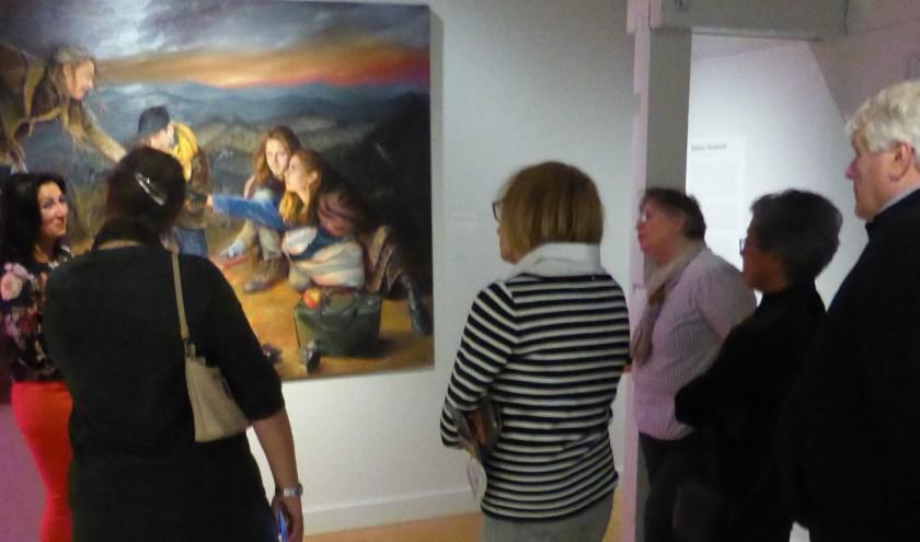 Suzana Jovanovic (uiterst links) vertelt aan bezoekers van het Museum Jan Cunen meer over de totstandkoming van haar schilderij. Het werk is tot en met komend weekend bij het Osse museum te zien.