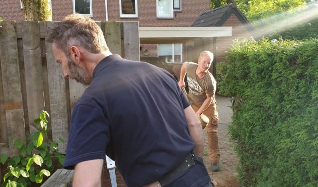 De vrijwilligers knappen de tuin op