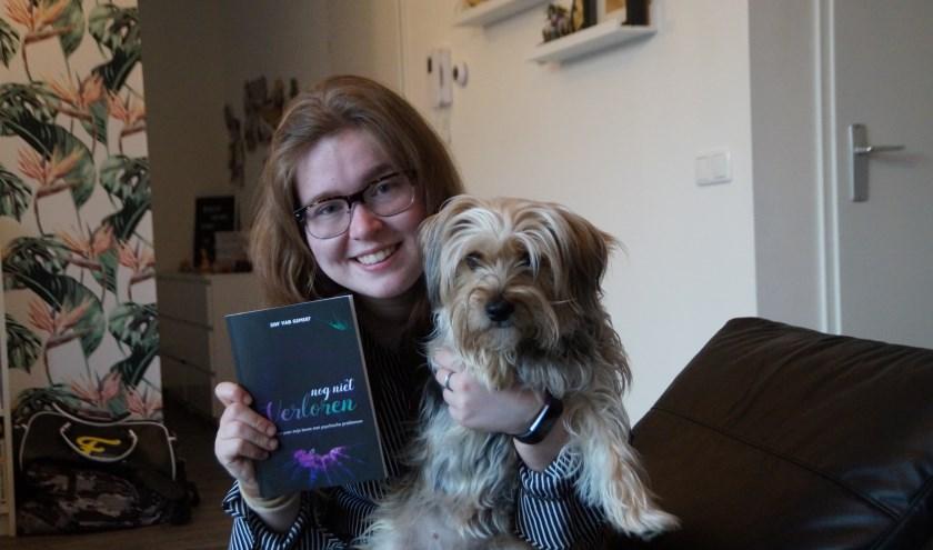 Sidy van Gemert, samen met haar hond Puck die juist in duistere dagen een belangrijke steun voor haar is. In haar hand haar gedichtenbundel 'Nog niet verloren'.