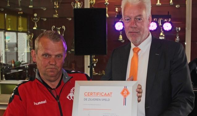 Jan Hollink heeft zondag uit handen van KNVB-ambassadeur Klaas Jansen de zilveren speld en een oorkonde van de KNVB gekregen.