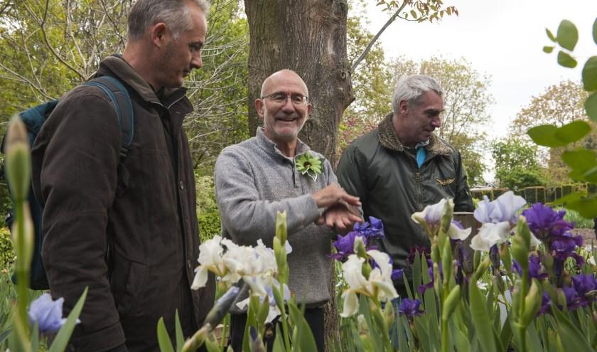 Loïs Tasquier. (tweede van links) leidt  bezoekers rond in zijn grote tuin in Gendt. Kijken kan ook zondag nog. (foto: Ellen Koelewijn)
