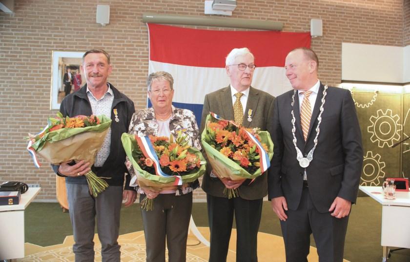 Burgemeester Rik de Lange reikte de versierselen uit in de raadzaal van het gemeentehuis aan het echtpaar Stokman (midden) en Martin Jansen.