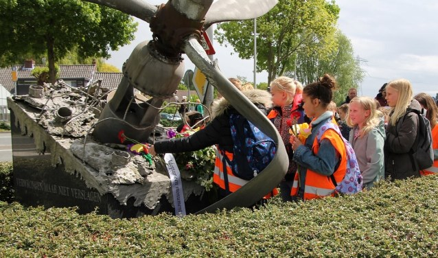 De leerlingen leggen hun eigengemaakte bloemen bij het monument. (Foto: Martin M. Marcus)