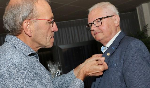 Herman ter Huurne is aangedaan als Harry Koopman de FKB erespeld op zijn revers bevestigt.