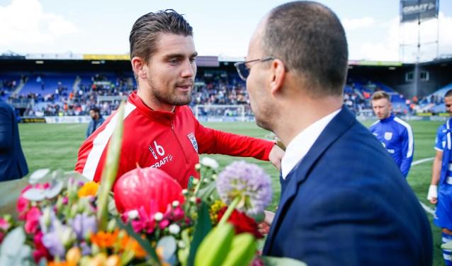 Mickey van der Hart krijgt de bloemen van technisch directeur Gerard Nijkamp.