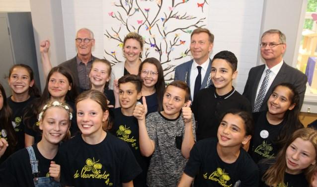 De kinderen van de Vuurvlinder poseren samen met burgemeester Kats, wethouder Verloop en de directie van de Vuurvlinder Wil Fritz en Marian Peters voor het onthulde schilderij.