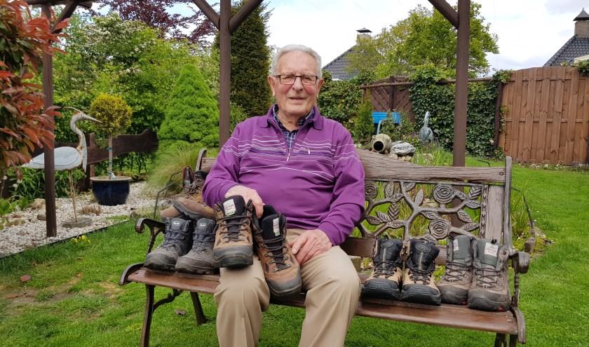 Pleun Kruidenier in zijn fraaie tuin, omringd door zijn vele wandelschoenen. 'Ik loop en fiets nog zoveel mogelijk.'