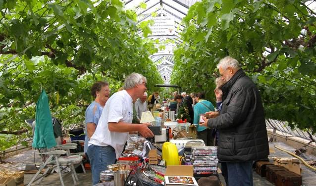 De druivenkas van Mea Vota vormt een bijzonder decor voor de snuffelmarkt van het Lingewaards Mannenkoor. (foto: Kirsten den Boef)