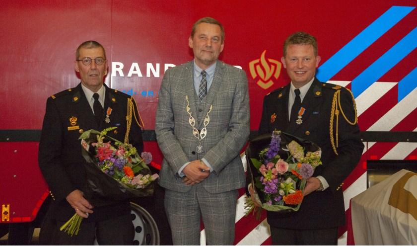 De brandweerlieden Harm Hoftiezer en Bas Kempers ontvingen een lintje en bloemen uit handen van burgemeester Anton Stapelkamp.