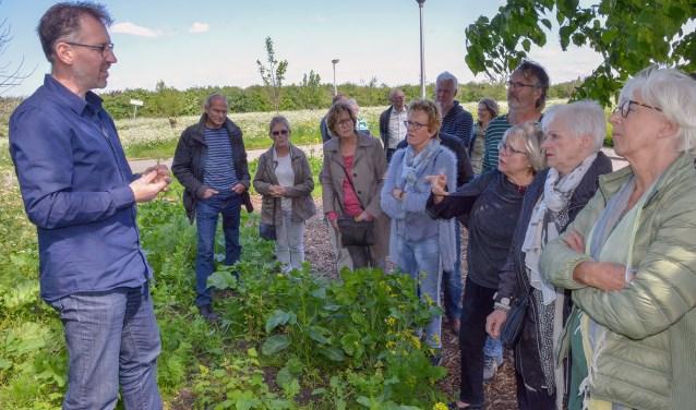 Geral Overbeek (l) laat zijn toehoorders zien en proeven wat er in de tuin op de hoek van het Toleind allemaal aan eetbare gewassen groeit en bloeit. (Foto: Paul van den Dungen).