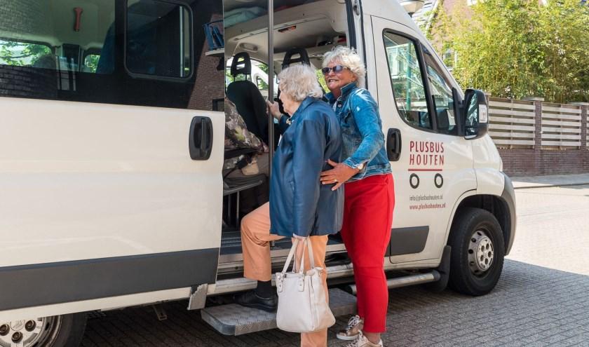 Henny Diepstraten helpt een passagier de Plusbus Houten in. Foto: Rene van den Brandt.