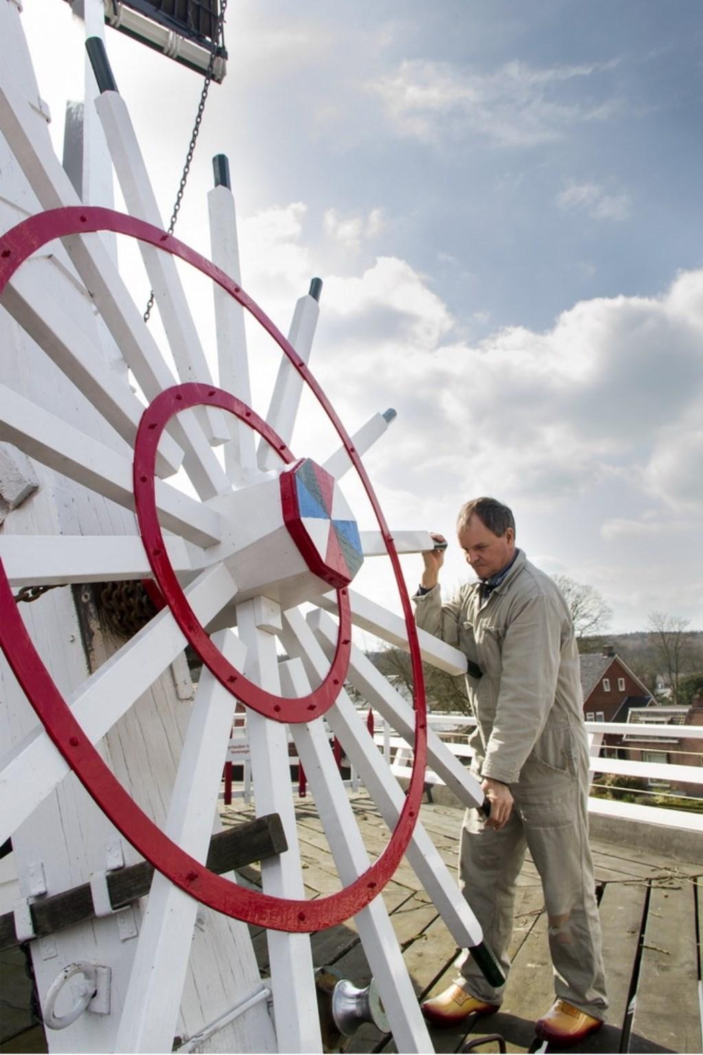 Molenaar Jan van de Beld druk aan het werk bij 'zijn' molen. Foto: Vrienden van de molen © Persgroep