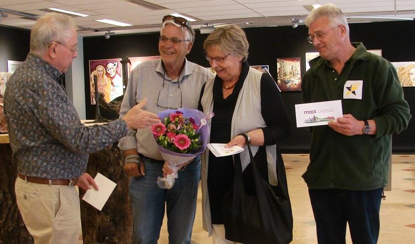 Joop Huisman (links) verrast het echtpaar Cremer uit Haren (Groningen) met een mooi boeket bloemen en een tegoedbon voor een lunch bij lunchroom Lievestro. Wim Slotboom overhandigt namens de VVV een bon van de Stichting Mooi in Ruurlo.