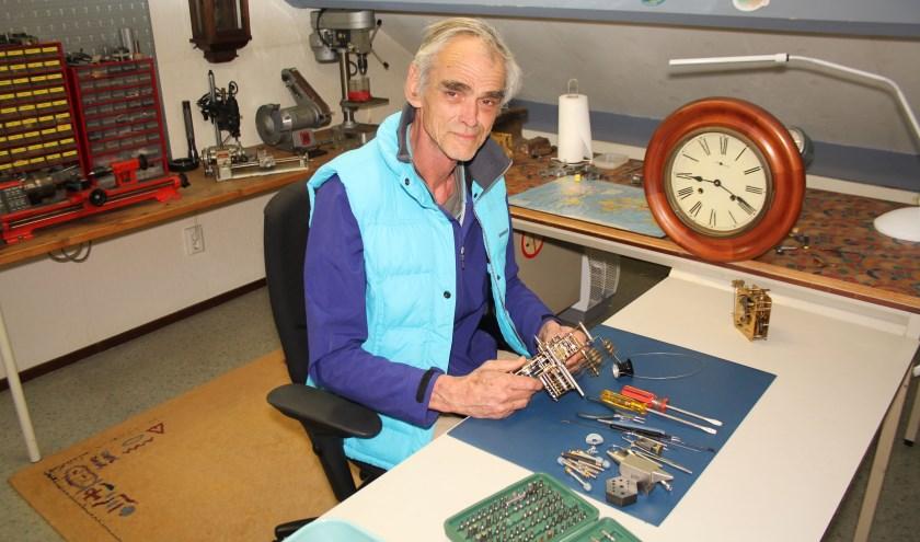 Jacques Wachter aan het werk. Met op de achtergrond de klok waar zijn hobby jaren geleden mee begon. (Foto: Lysette Verwegen)
