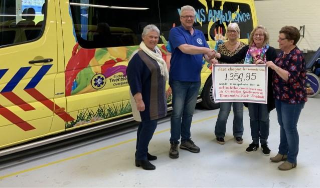 Vrijwilliger Henk en een aantal leden van de ActiviteitenCommissie bij het overhandigen van de symbolische cheque.