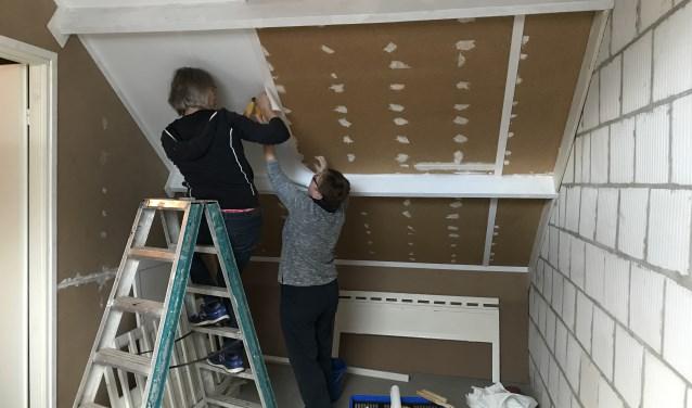Twee vrijwilligers behangen de schuine zolderwand. (foto: Present Bronckhorst)