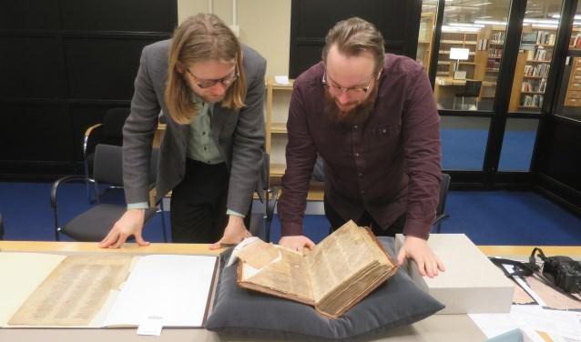 Daan Doesborgh (rechts) en Stef Uijens bestuderen het fragment dat zij hebben ontdekt in de Koninklijke Bibliotheek.
