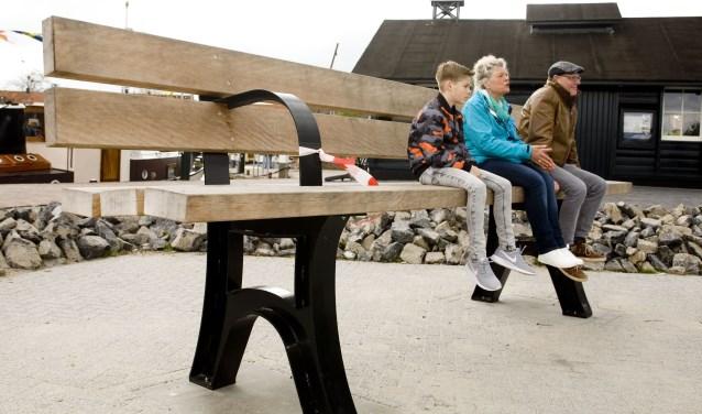 De 'afscheidsbank' in de haven van Elburg. Met v.l.n.r.: jeugdburgemeester Jesse Moling, José Oosthoek en Hans Kleijer van Paperclip Design. (Foto: Fotostudio Ger Hup)