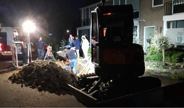 Buurtbewoners kijken rond elf uur 's avond in het Oosteinde naar de werkzaamheden van Liander. (foto: Danny van der Kracht)