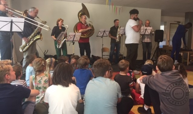 De kinderen maken kennis met verschillende instrumenten zoals de 'dikke trompet' (sousafoon).