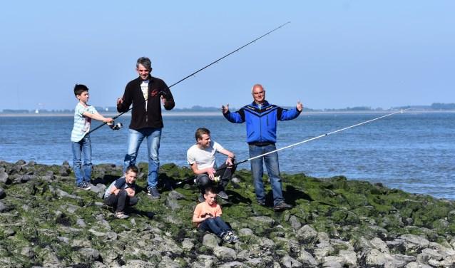 John Pieper (links in het zwart) en Jan Lindhout (rechts) van de hengelsportvereniging Reimerswaal organiseren elk jaar het Open Zeeuws Jeugdkampioenschap Kustvissen. FOTO: Rachel van Westen