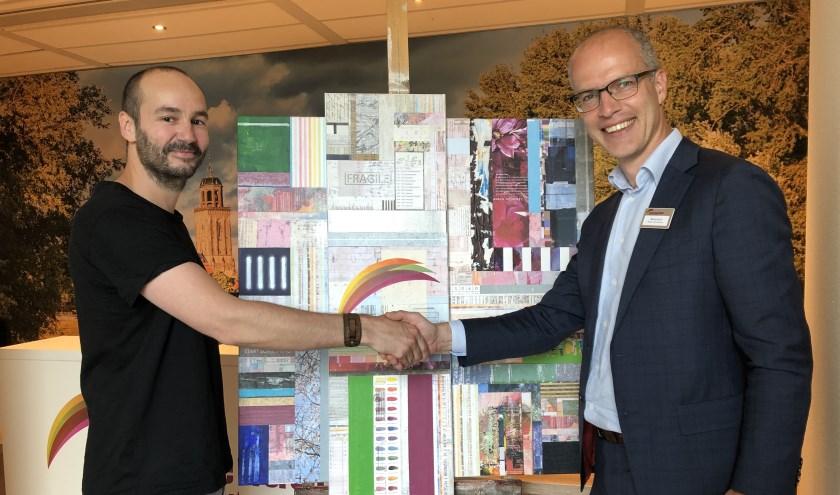 """Kunstenaar Wouter van Donselaar en bestuurder Martijn Kuit schudden elkaar de hand voor het kunstwerk """"KRACHT""""."""